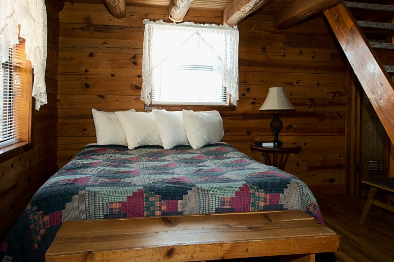The queen bed on Cabin 2's main floor; in the loft are two full-size beds