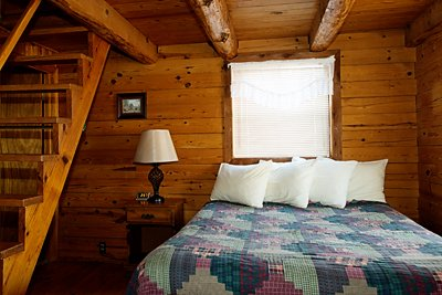 The queen bed on the main floor of Cabin 4