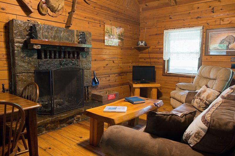 The living area of the cabin features a comfy sofa and native-stone fireplace.