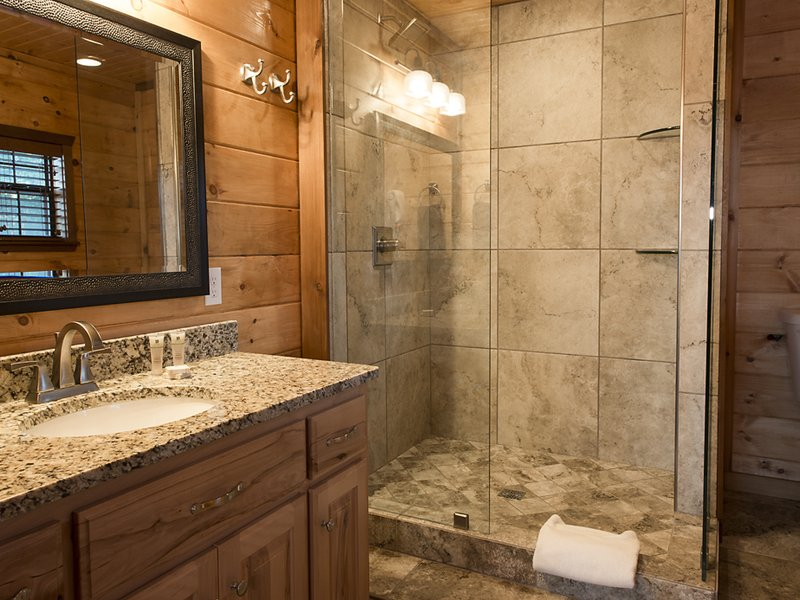 The cabin's bath features a spacious stone-tiled shower