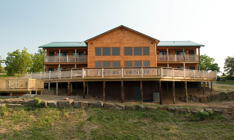 The lodge features a large deck with dining rail.  The hot tub deck can be seen at lower left.