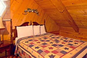 The cabin's queen bed in the loft (with bathroom adjacent)